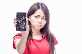 picture of frown  - Frowning Chinese woman holding cell phone with cracked screen - JPG
