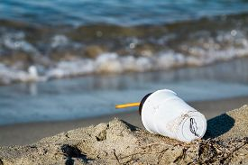 picture of polution  - Plastic coffee cup garbage with kelp on the beach behind blue sea wave blur - JPG