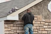 foto of stone house  - man working on completing stone work on new home - JPG