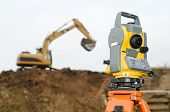 picture of theodolite  - Surveyor equipment theodolite on tripod at building area in front of working construction machinery loader - JPG