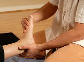pic of foot massage  - therapist giving a foot massage to client - JPG