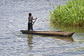 picture of hollow log  - A young boy wearing short pants paddles a traditional bwato or dugout canoe hollowed form a log past a reed bed in Lake Malawi Africa - JPG