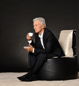 pic of debauchery  - Portrait of a senior man with cap of coffee over a black background - JPG