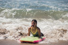 stock photo of boogie board  - Girl child landing in the sand as she rides the boogie board - JPG