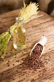 image of flax seed oil  - Vertical photo with a bunch of flax plants with dried blooms bonded by natural cord placed on old wooden board and with burlap around which is near to bottle with flax oil and heap of flax seeds - JPG