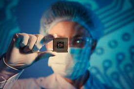 stock photo of microchips  - Computer engineer holding microchip for detailed analysis on the foreground - JPG