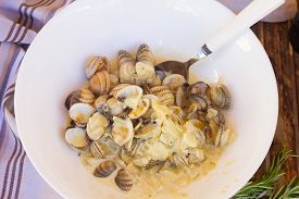 foto of shell-fishes  - Clam shell fish in big white plate with spoon - JPG