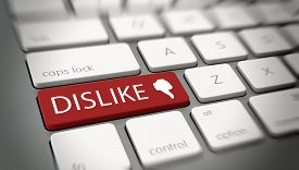 stock photo of dislike  - Online or internet Dislike concept for social media with a red enter button on a white computer keyboard with the words  - JPG
