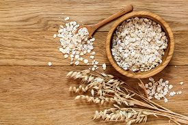 picture of oats  - Rolled oats and oat ears of grain on a wooden table copy space - JPG