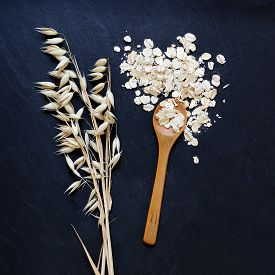 stock photo of oats  - Rolled oats and oat ears of grain on black background - JPG
