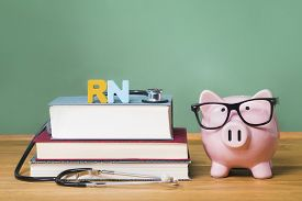stock photo of rn  - Registered Nurse RN theme with pink piggy bank with chalkboard in the background as concept image of the costs of education - JPG