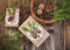 stock photo of cone  - Hand crafted gift on rustic wooden background and a basket with fir branches and cones - JPG