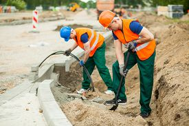 stock photo of labourer  - Photo of labourers working on a road construction - JPG