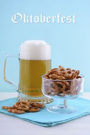 pic of stein  - Glass of beer in stein with mini pretzels on pale blue napkin on pale blue and white wood background with sample text - JPG