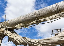stock photo of sailing vessels  - Old ragged sailing rigging an ancient sailing vessel against cloudy sky - JPG