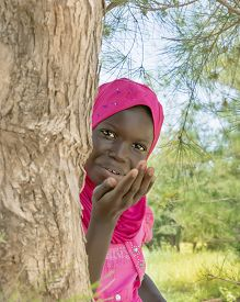 pic of ten years old  - Afro girl sending a kiss from behind a filao tree - JPG