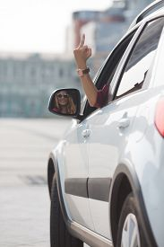 pic of fuck  - Pretty lady looking at side mirror of her car and showing middle finger - JPG