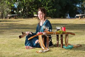 pic of sabbatical  - Caucasian adult outdoors with feather and pagan altar - JPG