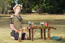 stock photo of sabbatical  - Cute pagan woman with wreath sitting at outdoor altar - JPG
