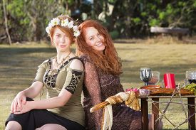 picture of sabbatical  - Pair of smiling women at outdoor pagan altar - JPG