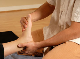 stock photo of thai massage  - therapist giving a foot massage to client - JPG