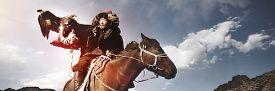 stock photo of mongolian  - Mongolian Man Trained Eagle Kazakh Olgei Western Concept - JPG