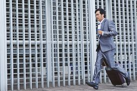 picture of running-late  - Vietnamese businessman with suitcase running late for flight - JPG