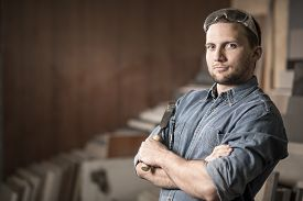 foto of chisel  - Young worker standing with a chisel in workshop - JPG
