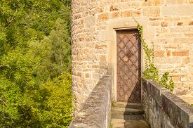 stock photo of old stone fence  - Old castle tower entrance with a stone bridge and forest in the background - JPG