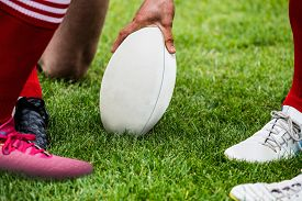 stock photo of huddle  - Rugby players in huddle with ball at the park - JPG
