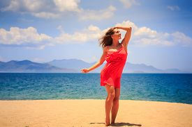 pic of long distance  - blond slim girl in short red frock stands on sand touches head looks into distance against sea wind shakes long hair - JPG
