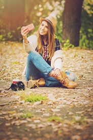 foto of takeaway  - Beautiful fashionable teenage girl taking a selfie with smartphone sitting in park in autumn with digital camera and takeaway coffee next to her - JPG