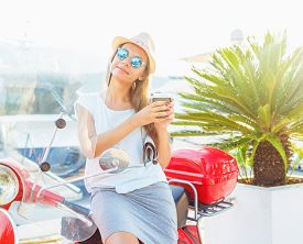 stock photo of takeaway  - Happy young trendy woman drinking takeaway coffee near her red moped on the waterfront in the morning  - JPG