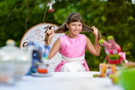 stock photo of alice wonderland  - Girl sits at table and pulls her hair - JPG