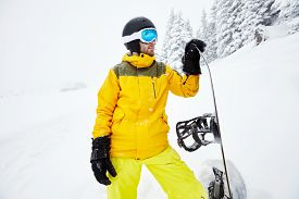 stock photo of extreme close-up  - Close up portrait of male snowboarder wearing helmet with glasses - JPG