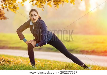 poster of Young woman stretching and warming up at park during sunset. Attractive girl stretching before fitne