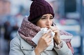 Young woman coughing during winter on street. Girl with cold wearing knitted cap and scarf feeling u poster