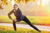 Young woman stretching and warming up at park during sunset. Attractive girl stretching before fitne poster
