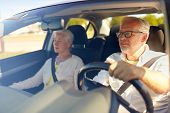 road trip, travel and old people concept - happy senior couple driving in car poster