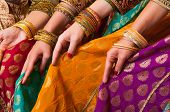 Bollywood dancers are holding their vivid costumes. Hands are in a row poster