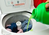 stock photo of washing machine  - Pouring green detergent into the washing machine - JPG