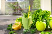 Glass of green healthy juice with fruits and vegetables on table poster