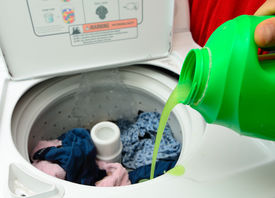 pic of washing machine  - Pouring green detergent into the washing machine - JPG