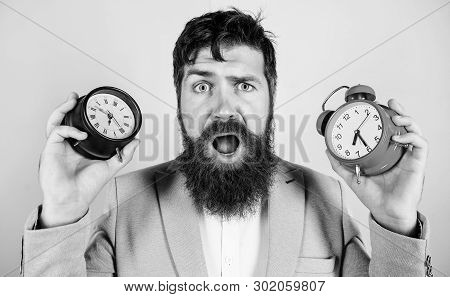 poster of Does Changing Clock Mess With Your Health. Man Bearded Hipster Hold Two Different Clocks. Guy Unshav