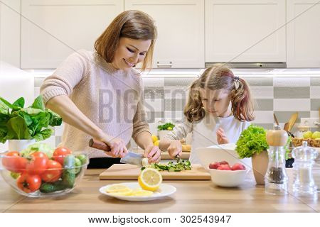 poster of Mother And Child Cooking Together At Home In Kitchen. Healthy Eating, Mother Teaches Daughter To Coo