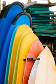 Set Of Multicolored Surf Boards In A Stack By Ocean.bali.indonesia. Surf Boards On Sandy Beach For R poster