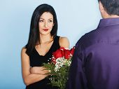 image of soliciting  - Young man giving skeptical girlfriend flowers - JPG