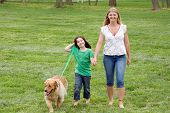 stock photo of mother child  - Mother and Daughter Walking the Dog in the Park - JPG
