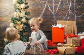 Funny Kid Holding Christmas Gift. Christmas Kids. Cute Little Child Is Decorating The Christmas Tree poster