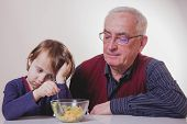 The Child Does Not Want To Eat And Has No Appetite. Grandpa Feeding His Grandchild With Fruits Salad poster